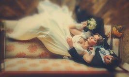 Braut und Bräutigam legen unvorsichtig auf das alte Sofa stockfotos