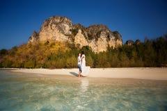 Braut und Bräutigam in Meer umranden gegen Klippen Stockfotos