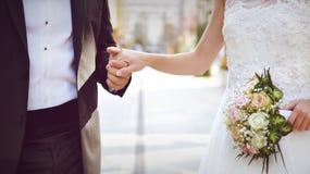 Braut und Bräutigam mit buntem Blumenstrauß Stockfotos
