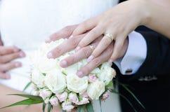 Braut und Bräutigam mit ihren Händen auf dem Blumenstrauß der Braut Stockbild