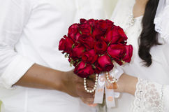 Braut und Bräutigam With Red Rose Bouquet Stockfotografie