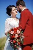 Braut und Bräutigam, reizendes Paar im Freien, heiratender Brautblumenstrauß mit roten Blumen Blauer Himmel, grünes Gras in einem Stockbild