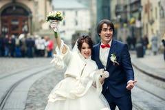 Braut und Bräutigam schauen die lustige Aufstellung auf dem alten Stadtplatz stockfotos