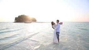 Braut und Bräutigam umarmen im Wasser am Spucken gegen Insel