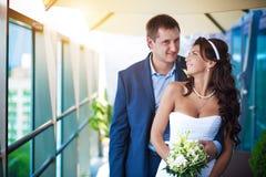Braut und Bräutigam umarmen nahe der Glaswand lizenzfreies stockfoto