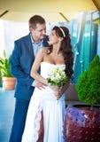 Braut und Bräutigam umarmen nahe der Glaswand lizenzfreie stockbilder