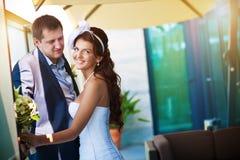 Braut und Bräutigam umarmt nahe dem Fenster lizenzfreie stockbilder