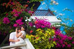 Braut und Bräutigam umfassen leidenschaftlich auf dem Balkon auf einem Hintergrund von Blumen stockfoto
