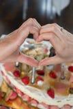 Braut und Bräutigam vor dem Kuchen, der ein Herz mit den Händen macht Stockbild