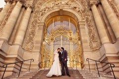 Braut und Bräutigam vor einem großen Gebäude Stockfotografie