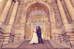 Braut und Bräutigam vor einem großen Gebäude Stockfotos