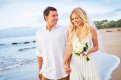 Braut und Bräutigam Walking auf schönem tropischem Strand bei Sonnenuntergang, R Lizenzfreies Stockfoto