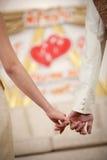 Braut und Bräutigam, welche die Handwarteheirat halten Stockfotografie