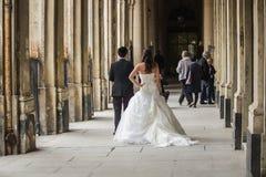 Braut und Bräutigam werfen für Heiratsschüsse unter Palais Royal-Säulengang auf Stockbilder