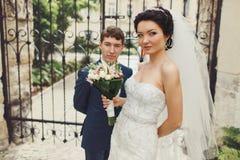 Braut und Bräutigam werfen Stellung auseinander in der Front von geschmiedeten Toren auf lizenzfreie stockbilder