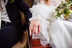 Braut- und Bräutigamhändchenhalten in einem Auto Stockbild