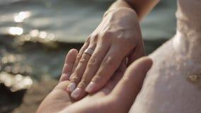 Braut- und Bräutigamhändchenhalten schließt oben am Strand stock video footage
