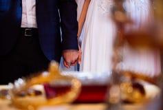 Braut- und Bräutigamhändchenhalten während der Hochzeitskirchenzeremonie Stockbilder