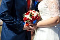 Braut- und Bräutigamhände, die Hochzeitsblumenstrauß halten selektiver Fokus Blumenstrauß zwischen der Braut und dem Bräutigam, N Stockfotos