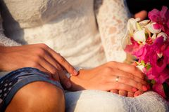 Braut- und Bräutigamhände mit Blumenstrauß Stockbilder