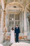 Braut- und Bräutigamlächeln, das in einem alten ruinierten Ziegelsteinfenster des alten Gebäudes steht Stockbilder