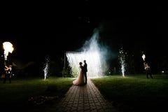 Braut- und Bräutigamstand nachts Heiratsbogen lizenzfreies stockbild