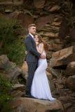 Braut- und Bräutigamumarmung auf einem Hintergrund von wilden Felsen in den Bergen lizenzfreies stockfoto