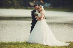 Braut- und Bräutigamumarmung stehend auf einem Seeufer Lizenzfreie Stockfotografie