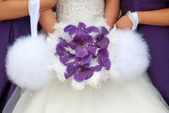 Braut und Brautjungfern mit purpurrotem Orchideenblumenstrauß Stockfoto
