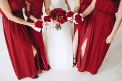Braut und Brautjungfern mit roten Blumensträußen von Rosen Stockfoto