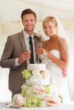 Braut und Bräutigam With Cake Drinking Champagne At Reception Stockbilder