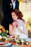 Braut und Bräutigam an der Hochzeitstafel Einstellung des Herbstes im Freien Lizenzfreie Stockbilder