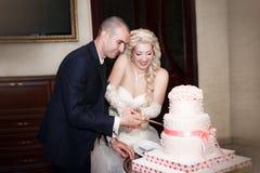 Braut und Bräutigam, die den Hochzeitskuchen schneiden Stockbild