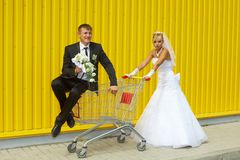 Braut und Bräutigam, die mit einem Korb des Supermarktes spielen Stockbild