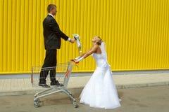 Braut und Bräutigam, die mit einem Korb des Supermarktes spielen Stockfoto