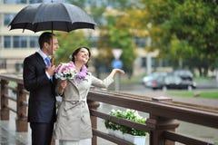 Braut und Bräutigam, die vom Regen, beim Abfangen von Regentropfen a sich verstecken Lizenzfreie Stockfotos