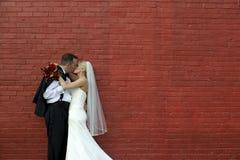 Braut und Bräutigam durch Backsteinmauer Stockbild