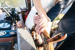 Braut und Bräutigam-Hand und auf einem Lenkrad Lizenzfreie Stockfotos