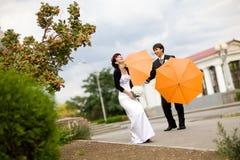 Braut und Bräutigam mit orange Regenschirmen Lizenzfreies Stockfoto