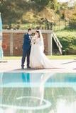 Braut und Bräutigam nahe dem Swimmingpool Bemannen Sie das Halten der Hand der Frau im schönen Kleid Lizenzfreies Stockfoto