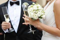 Braut- und Bräutigamholdingchampagnergläser Stockfotos