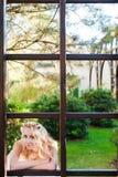 Braut und ein großer Rahmen des Fensters Stockfotos