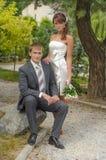 Braut und ihr Bräutigam, die auf einem Stein sitzen Lizenzfreie Stockfotografie