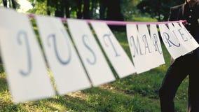 Braut und nevesat mit einem Zeichen gerade geheiratet stock video