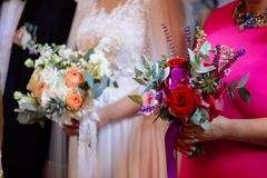 Braut und Patin, die Hochzeitsblumensträuße während der Hochzeitszeremonie halten Lizenzfreies Stockfoto