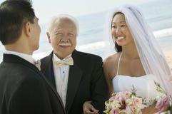 Braut und Vater mit Bräutigam an der Strandhochzeit stockfotos