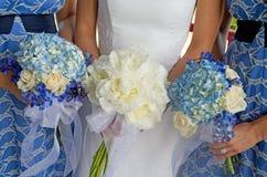 Braut und zwei Brautjunfern, die Blumensträuße anhalten Lizenzfreies Stockfoto