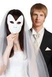 Braut verstecktes Gesicht hinter Schablone; Bräutigam steht nach Stockbilder
