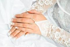 Braut, welche die Hände auf einem weißen Hochzeitskleid anhält Lizenzfreie Stockfotos