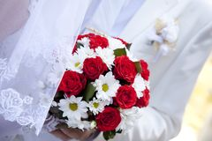 Braut, welche die schönen roten Rosen wedding sind Blumenstrauß anhält Lizenzfreies Stockbild